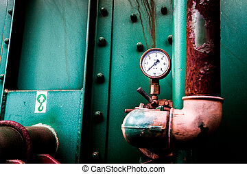 Pressure gauge on a machine with an older industrial plant.