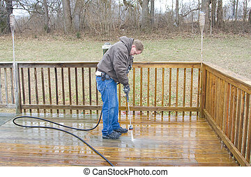 Worker pressure washing deck on rear of house