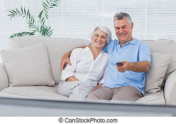 prestar atenção televisão, par, sofá, sentando