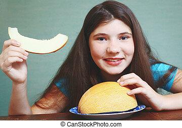 preteen beautiful girl with long dark hair slice of melon