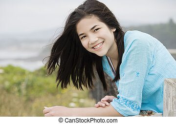 Preteen biracial girl with a beautiful smile, overlooking the ocean shore