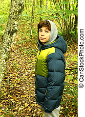 preteen boy close up portrait in the autumn forest