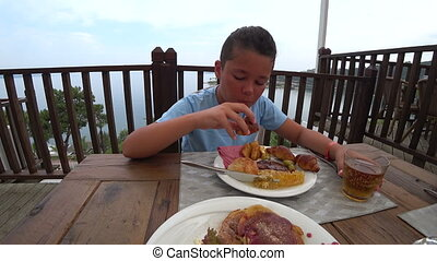 Preteen boy eating breakfast at the outdoor - Young boy...