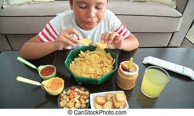Preteen boy eating nachos - Young boy eating unhealthy...