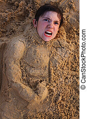 preteen boy head in  the beach sand happy smiling