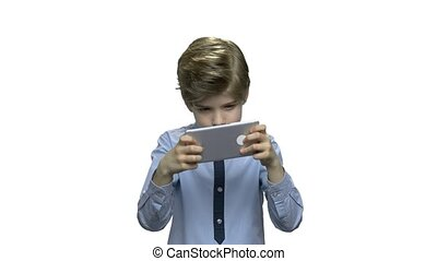 Preteen boy playing game on smartphone. Handsome kid...