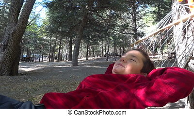 Preteen boy relaxing on hammock - Portrait of a young boy...