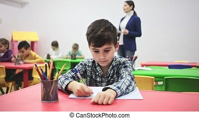 Preteen boy studying in classroom on background with ...