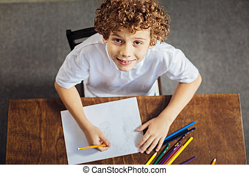 Preteen boy with curls looking into camera with slight smile