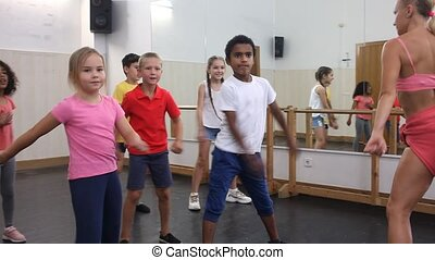 Preteen boys and girls with female trainer practicing floss dance movements, swinging hips and arms during group class. High quality FullHD footage