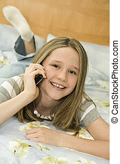 Preteen - Caucasian preteen girl laying in bed talking on a ...