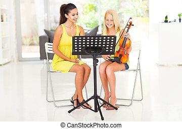 preteen girl having violin lesson - beautiful young pretty...