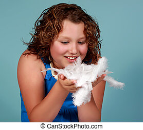preteen girl holding white feathers
