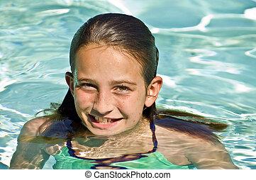 Preteen Girl in a Pool - A beautiful smiling preteen girl in...