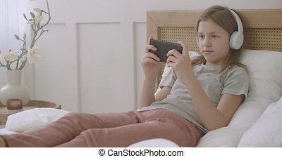 preteen girl is playing game in mobile phone, lying on bed in home after school classes, children with pathological internet use, laze and relax time
