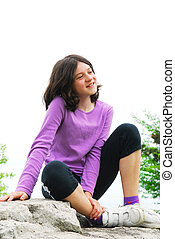 Preteen girl - Portrait of a young girl sitting on a rock...