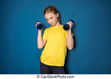 preteen girl training with dumbbells in studio isolated on blue