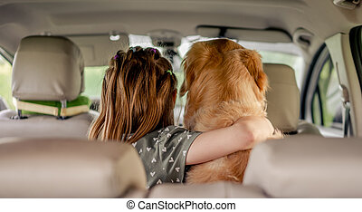 Preteen girl with golden retriever dog in the car