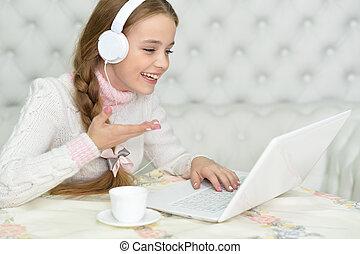 Preteen girl with laptop - Happy preteen girl in headphones...