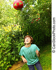 boy playing with ball training soccer head blow