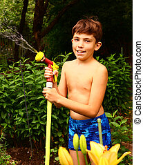 boy with watering pipe on the green garden background