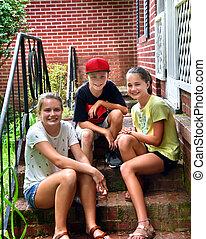 Preteens sit on Steps