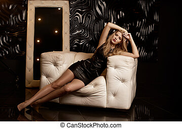 Prett young girl in short black dress on the sofa