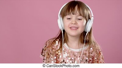 Pretty 6 or 7 years old little girl singing and dancing with...