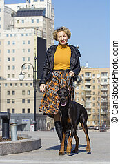 Pretty adult woman with dog outdoors