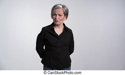 Pretty adult woman with gray hair showing facial expressions...