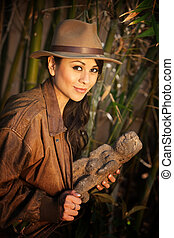 Pretty adventurer with stolen relic in thick green bamboo...
