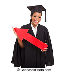 african american college graduate holding red arrow