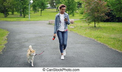 Pretty African American girl in denim jacket and jeans is...