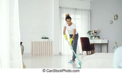 Pretty African American girl is mopping floor at home with...