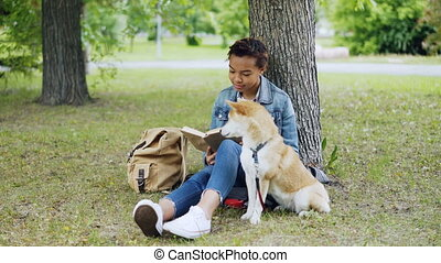 Pretty African American girl student is reading book sitting in park on lawn while her well-bred dog is sitting near her and smelling air and looking around.