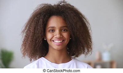 Pretty african american teen school girl looking at camera,...