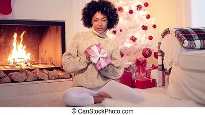 Pretty african american woman holds christmas gift while...