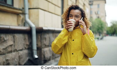 Pretty African-American woman is drinking to-go coffee and chatting on mobile phone walking in the city in spring wearing bright jacket. Modern technology and millennials concept.