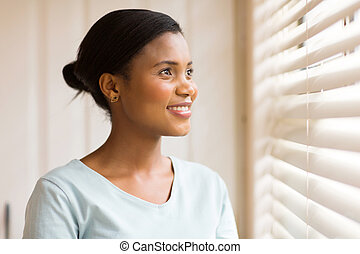 african american woman looking through the blinds