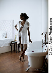 Pretty african american woman standing by the bathtub in the bathroom