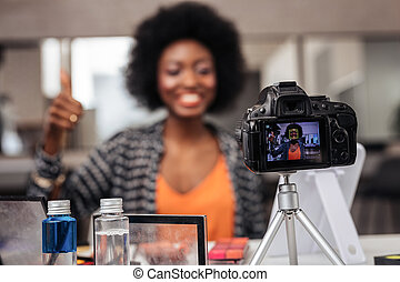 Pretty african american woman with curly hair making a video content for beauty blog