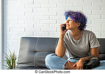 pretty african american woman with mobile phone at home sitting on the sofa