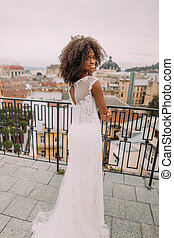 Pretty african bride in vintage lace dress posing for camera on the terrace