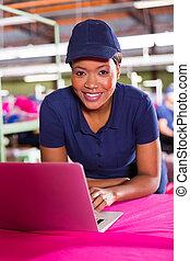 african clothing factory designer using laptop computer