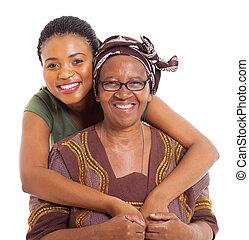 pretty african daughter hugging senior mother