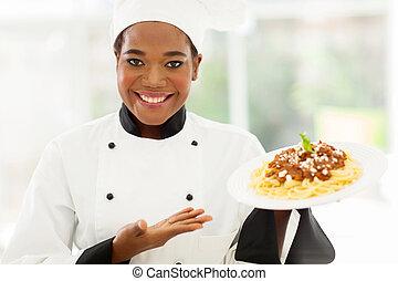 african female chef holding spaghetti dish