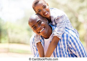 african woman enjoying piggyback ride on boyfriend