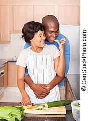 african woman feeding boyfriend slice of cucumber