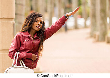 african woman hailing a taxi cab