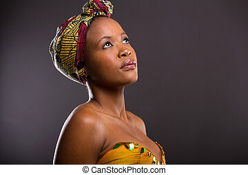 pretty african woman looking up on black background